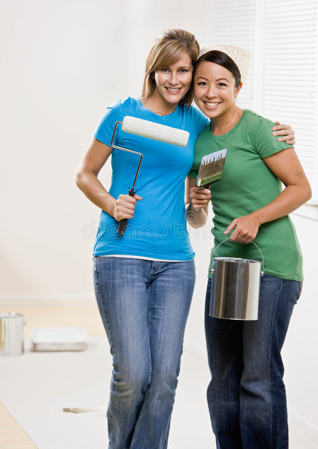 Self-sufficient friends painting with paint roller. And paint brush and paint can and renovating home royalty free stock images