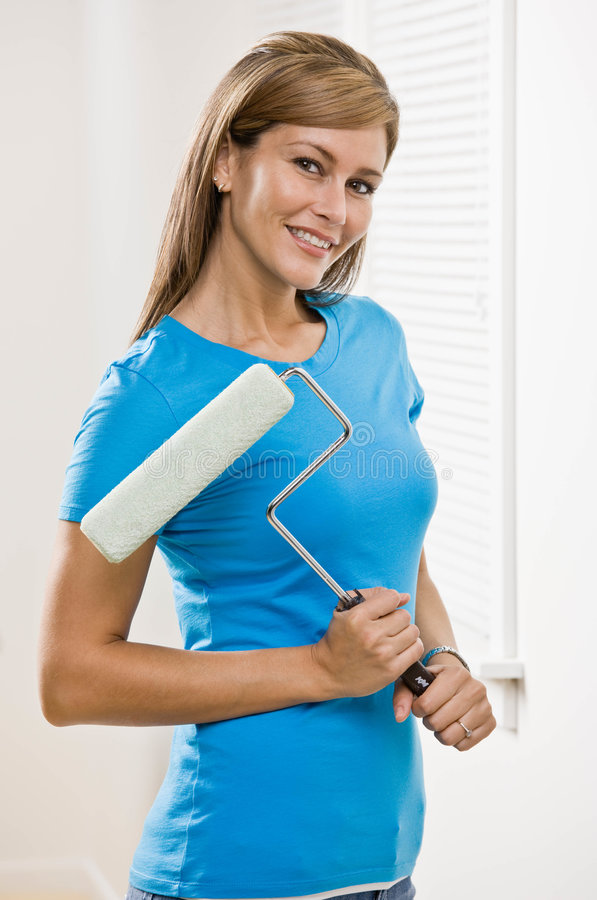 Self-sufficient woman holding paint roller. And renovating home royalty free stock photo