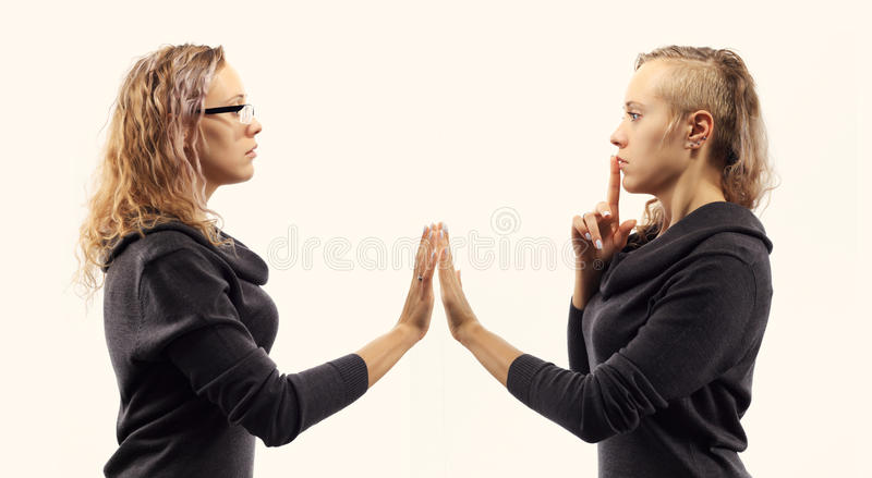 Self talk concept. Young woman talking to herself, showing gestures. Double portrait from two different side views. Self talk concept. Young blond caucasian royalty free stock photo