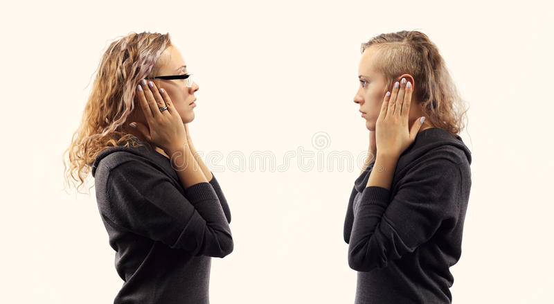 Self talk concept. Young woman talking to herself, showing gestures. Double portrait from two different side views. royalty free stock images