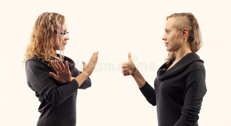 Self talk concept. Young woman talking to herself, showing gestures. Double portrait from two different side views. stock photos