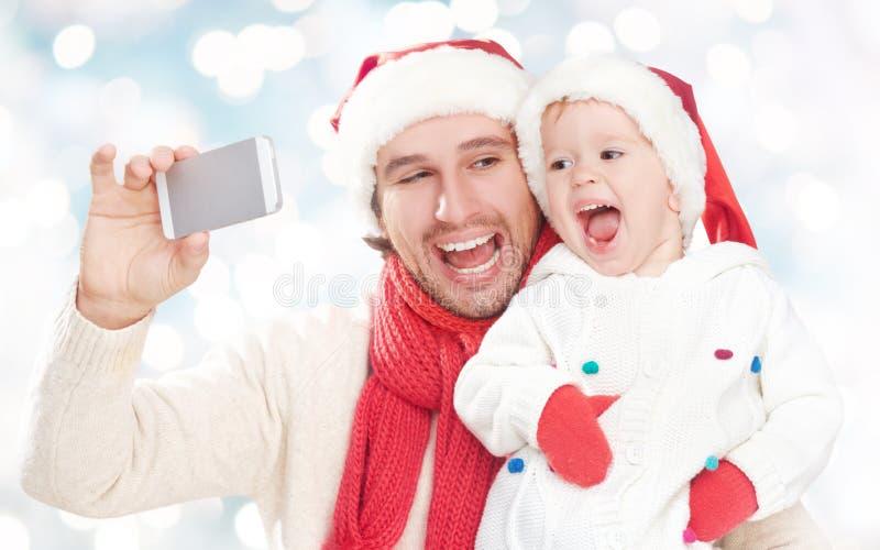 Selfe в зиме счастливый папа семьи играя с дочерью и сфотографированный на мобильном телефоне стоковая фотография