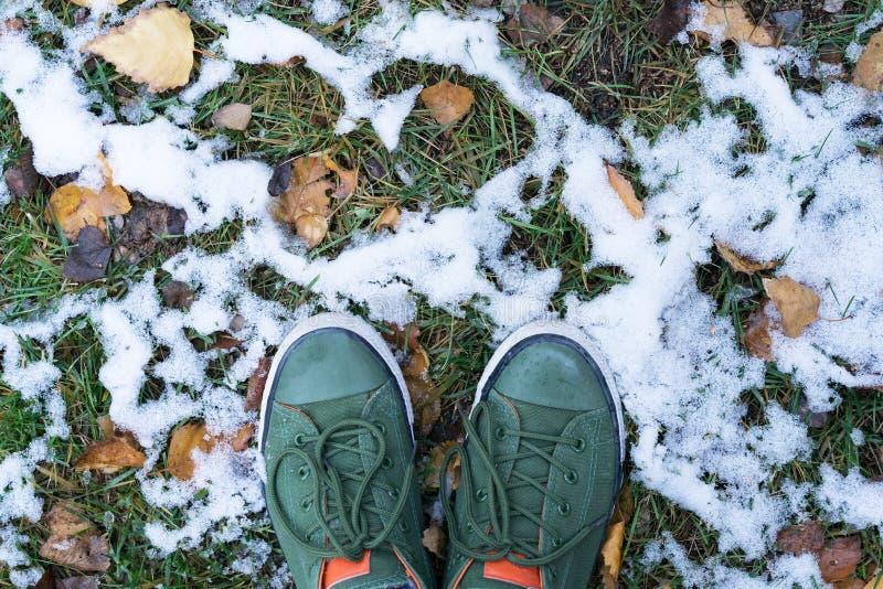 Selfi-Beine clouse oben in den grünen Turnschuhen, die im grünen Gras, in den gelben gefallenen Blättern und im ersten Schnee ste stockfoto