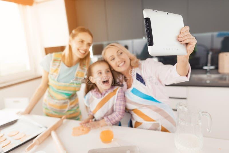 Selfi en la tableta Una mujer mayor decidía hacer un selfie con su hija y nieta foto de archivo libre de regalías