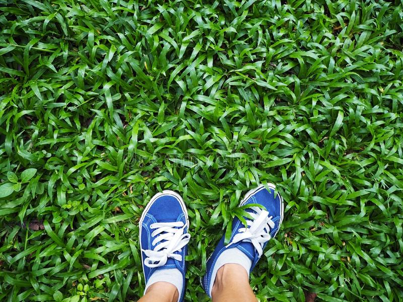 Selfie佩带在绿草的妇女脚蓝色运动鞋 图库摄影