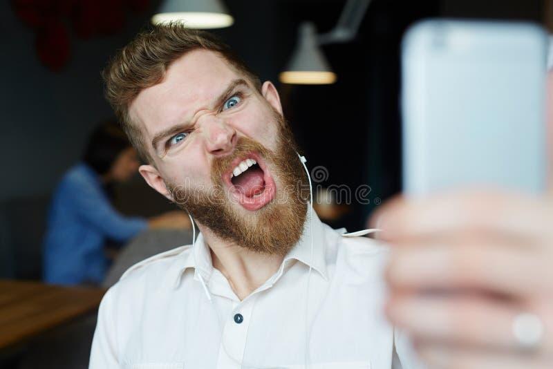 Selfie射击的恼怒的鬼脸 图库摄影