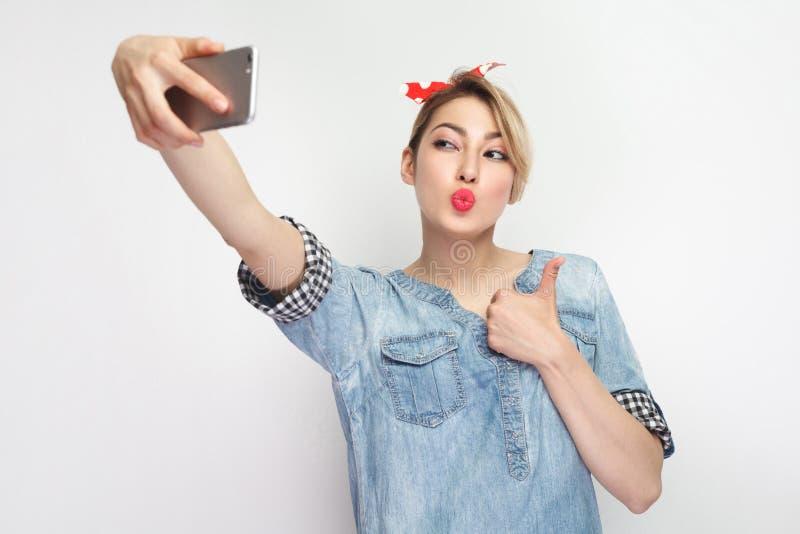 Selfie时间!性感的可爱的博客作者妇女画象偶然蓝色牛仔布衬衣的有构成的,红色头饰带身分,举行 库存图片