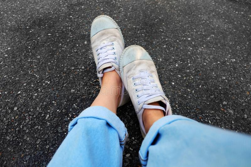 Selfie白色鞋子 关闭女服白色运动鞋和蓝色牛仔裤在混凝土路背景 图库摄影