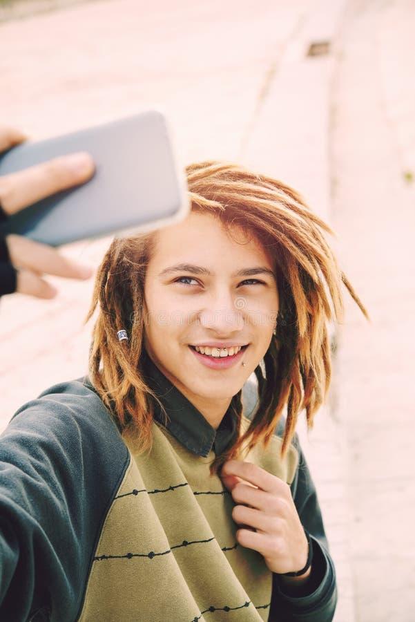 Selfie парня красивого rasta предназначенное для подростков в фильтре города теплом прикладном стоковое изображение