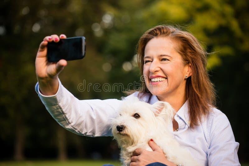 Selfie -资深妇女和狗 免版税库存照片