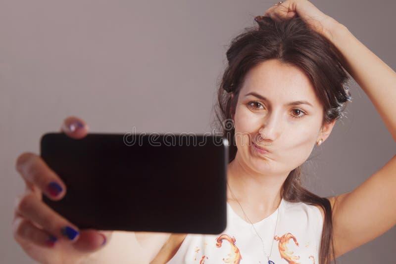Selfie?? 迷住采取在智能手机的白种人妇女画象selfie 免版税库存图片