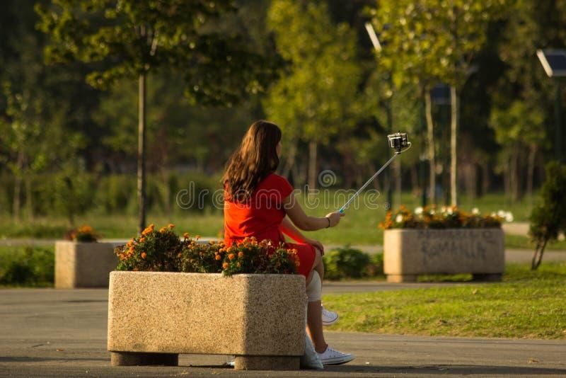 Κορίτσι που χρησιμοποιεί selfie το ραβδί στο πάρκο στοκ φωτογραφίες με δικαίωμα ελεύθερης χρήσης