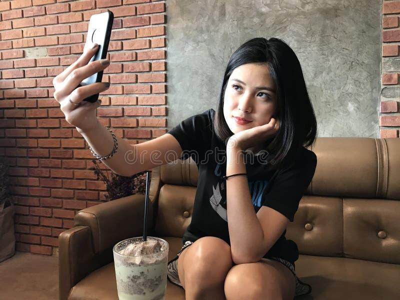 Selfie adolescente bonito asiático da mulher com telefone esperto fotografia de stock