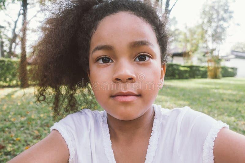 Selfie afro-americano da menina da raça misturada da criança exterior foto de stock