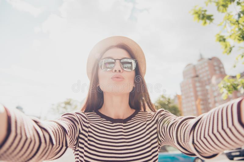Selfie and an air kiss! Young cute lady is photographing outdoor. S in the summer city, wearing casual spring outfit, trendy hat and fashionable sunglasses royalty free stock photos