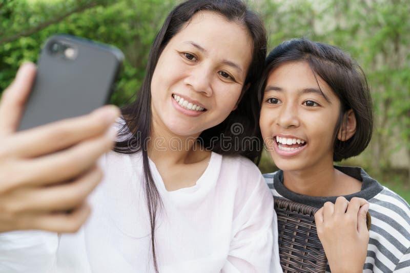 Selfie asiático de la madre y de la hija por smartphone junto en el jardín en casa Una muchacha y las mujeres sonríen al tomar la imagenes de archivo