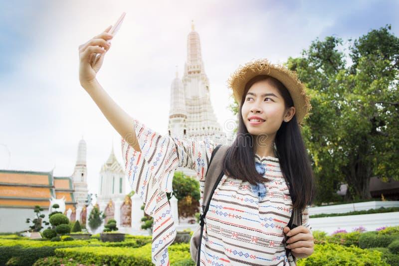 Selfie asiatico di viaggiatore con zaino e sacco a pelo delle donne durante il tempio di Wat Arun di viaggio fotografia stock