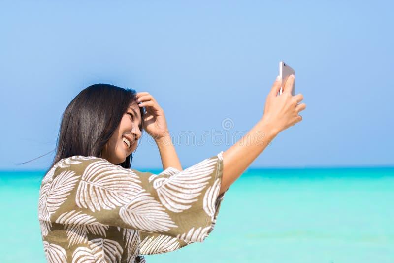 Selfie asiatico lei stessa delle donne sulla spiaggia Donne asiatiche felici per la t fotografie stock libere da diritti
