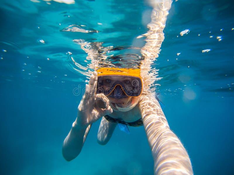 Selfie av den unga kvinnan som snorklar i havet G?ra allt ok symbol royaltyfri foto