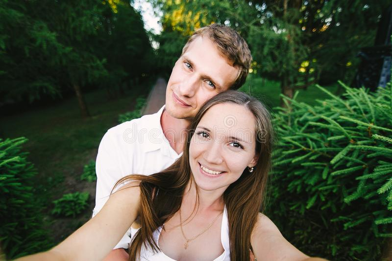 Selfie av ett trevligt par som ler att krama för ett skott arkivfoton