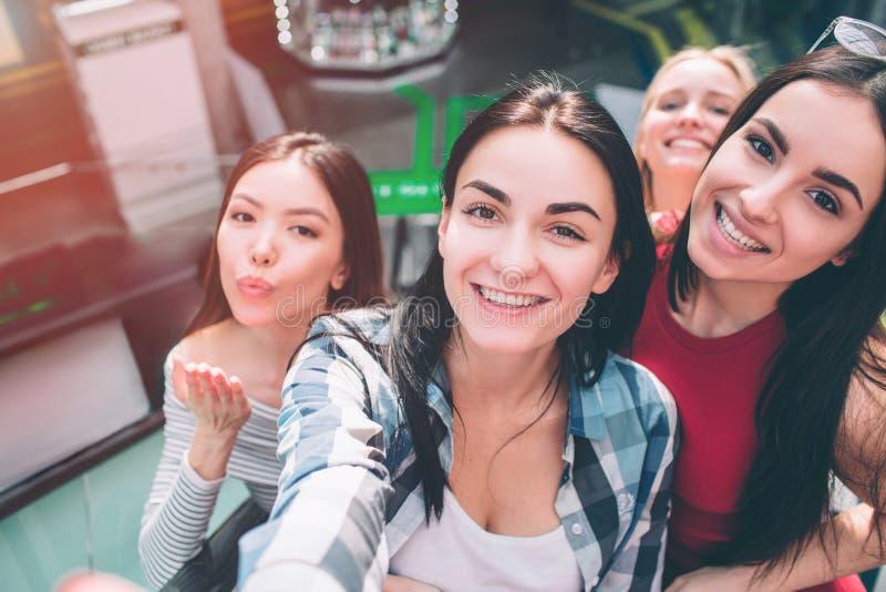 Selfie av fyra flickor som har gyckel tillsammans De poserar med leende, och överföra kysser till kameran royaltyfri fotografi