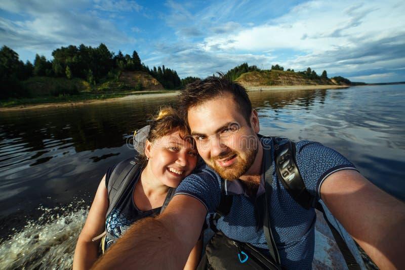 Selfie av lyckliga par under ridning på det motoriska fartyget Härlig flodstrand på bakgrund royaltyfri fotografi