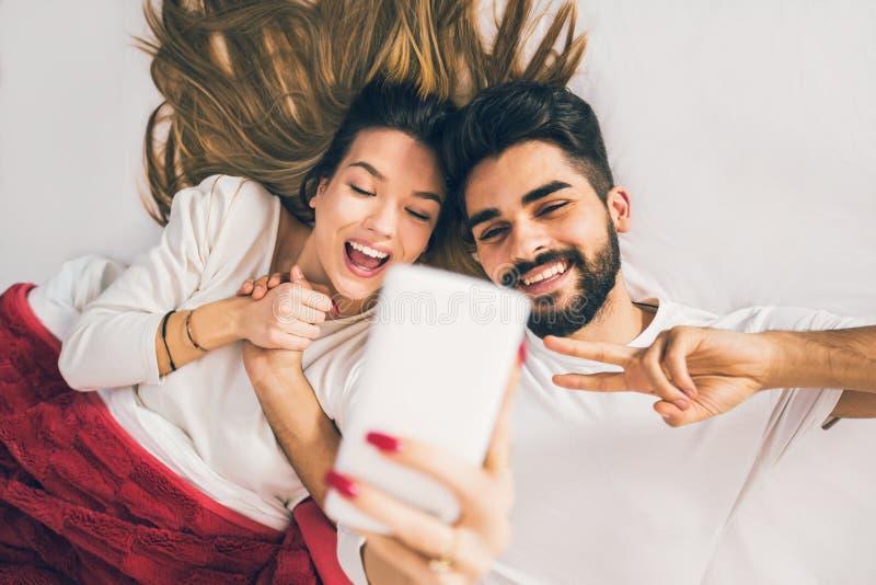 Selfie! Bästa sikt av härliga unga älska par som ligger i säng arkivbild
