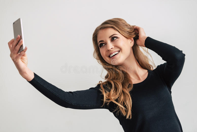 Selfie from beaut. Beautiful young woman making selfie while standing against white background stock images