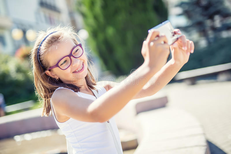 Selfie. Beautiful cute young girl with braces and glasses laughing for a selfie stock photo