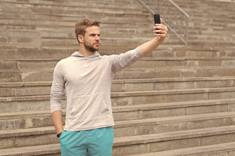 Selfie begrepp Stilig mantagandeselfie med smartphonen Idrotts- grabbbruksmobiltelefon f?r selfie Selfie f?r arkivfoto