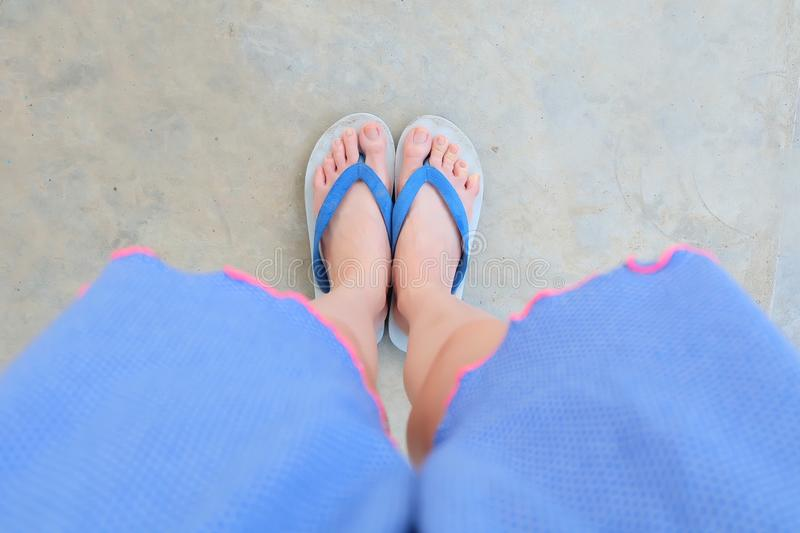 Selfie Blue Shoes on Concrete Floor for Top View. Woman's Feet Wearing Blue Pajamas and Flip Flop Slippers on The Cemen. T Floor Background Great For Any stock photo