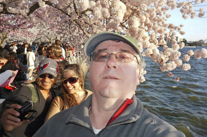 Selfie at the Cherry Blossoms. Photo of me as a selfie with other people in the background at the tidal basin in washington dc on 4/10/14. The cherry blossoms stock images