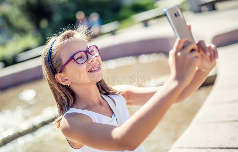 Selfie Chica joven linda hermosa con los apoyos y los vidrios que ríe para un selfie imágenes de archivo libres de regalías