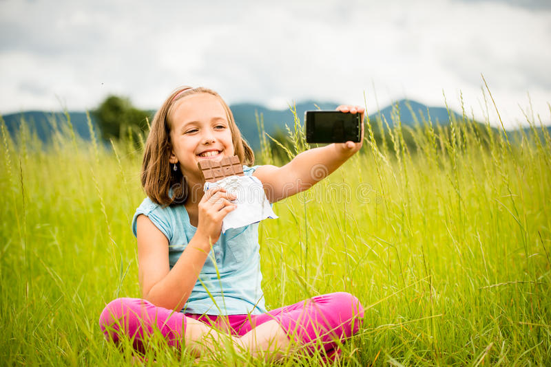 Selfie - child with chocolate. Child is taking photo with mobile phone camera while eating chocolate outdoor in nature royalty free stock photos
