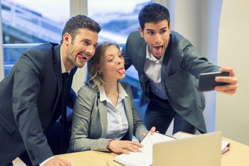Selfie commercieel team die beelden in het bureau nemen Hun tong royalty-vrije stock afbeelding