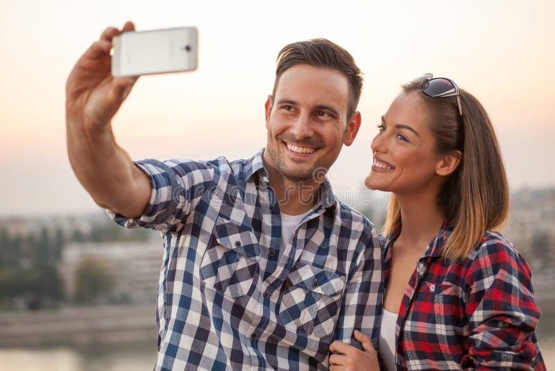 Selfie con Smartphone, par joven feliz imagen de archivo libre de regalías