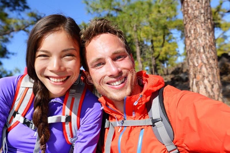 Selfie couple taking self-portrait hiking candid stock photo