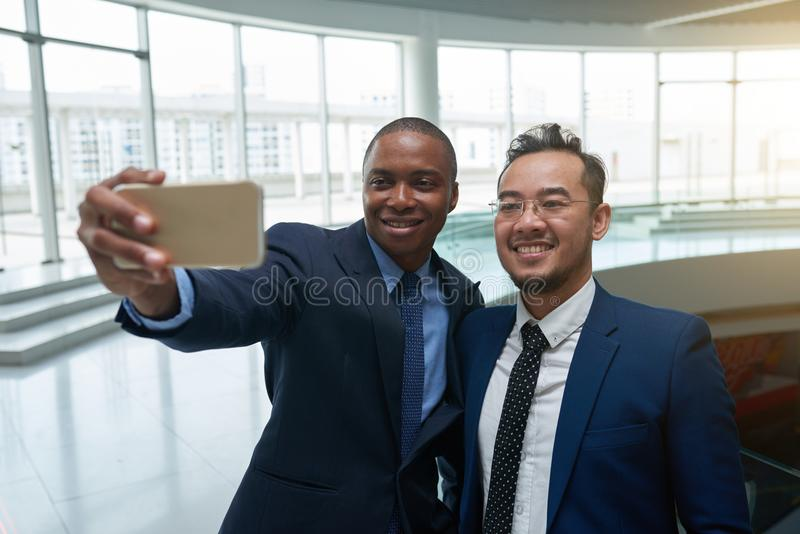 Selfie with coworker. Happt multi-ethnic business partners taking selfie in airport royalty free stock photos