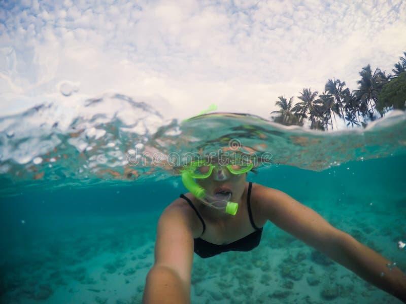 Selfie d'un touriste féminin de femme naviguant au schnorchel en mer bleue claire a photos stock