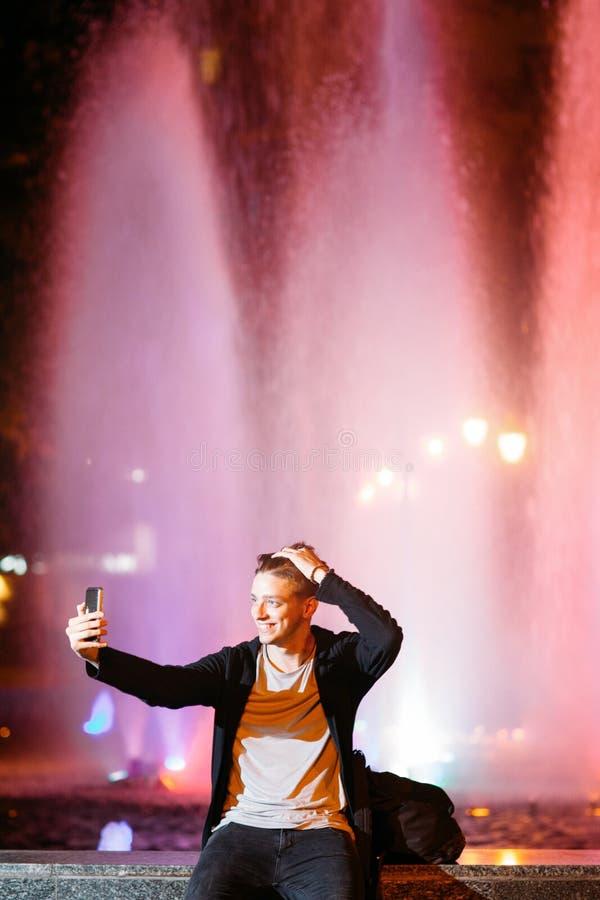 Selfie da tomada do homem novo no smartphone na cidade fotografia de stock royalty free