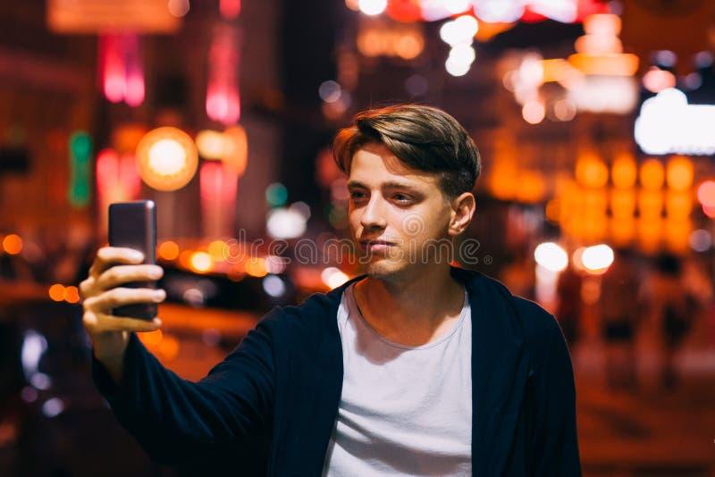 Selfie da tomada do homem novo no smartphone na cidade fotografia de stock
