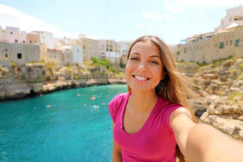 Selfie da tomada da jovem mulher em suas férias de verão em Polignano uma égua, mar Mediterrâneo, Apulia, Itália foto de stock