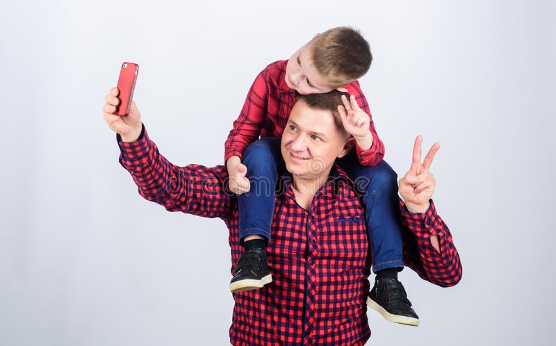 Selfie with daddy. fathers day. Enjoying time together. father and son in red checkered shirt. Happy family together. Small boy with dad man. childhood royalty free stock photography