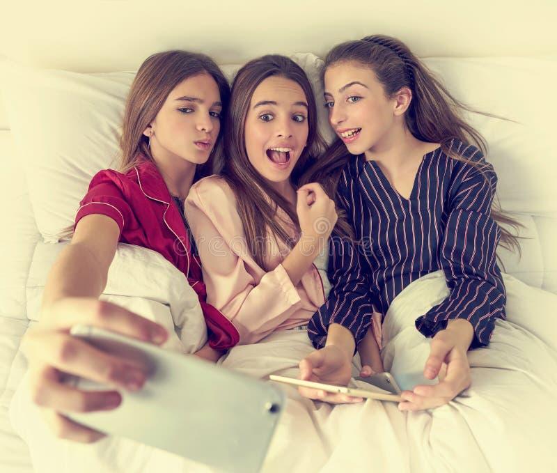 Selfie das meninas do melhor amigo do partido de pijama na cama foto de stock