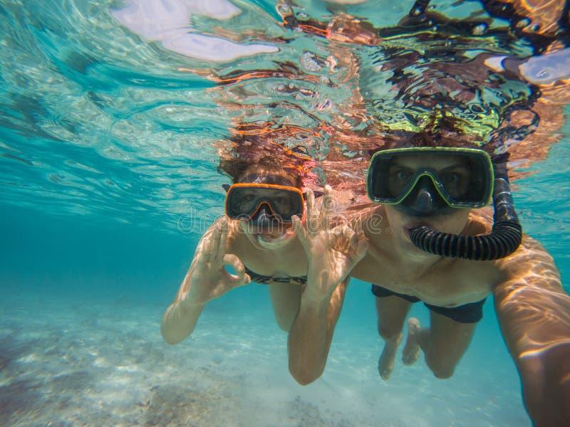 Selfie de jeunes couples naviguant au schnorchel en mer Faisant ? tout le symbole correct photographie stock libre de droits