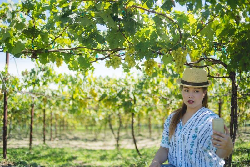 Selfie de la mujer del granjero con su teléfono en jardín de la uva fotografía de archivo libre de regalías