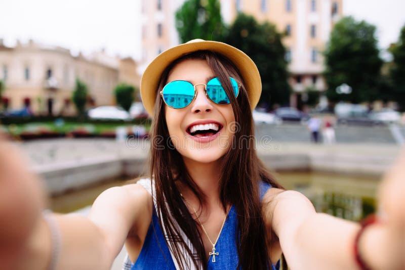 Selfie de la toma de la muchacha de las manos con el teléfono en la calle de la ciudad del verano fotografía de archivo