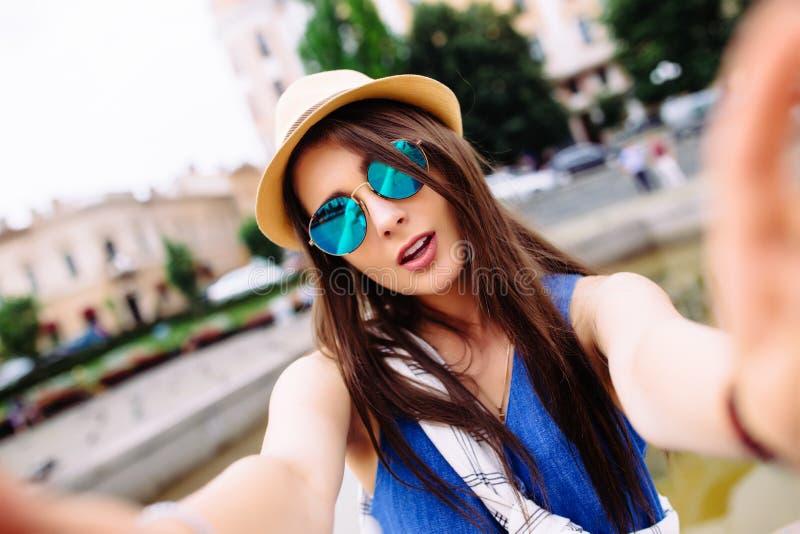 Selfie de la toma de la muchacha de las manos con el teléfono en la calle de la ciudad del verano imágenes de archivo libres de regalías