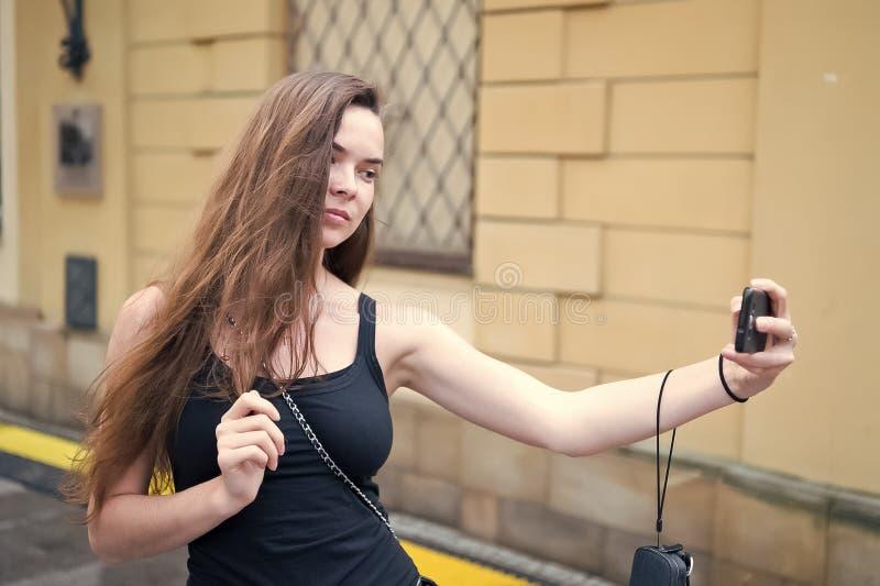 Selfie de la toma de la mujer con el teléfono móvil en la calle Mujer con smartphone largo del uso del pelo en al aire libre urba imagenes de archivo