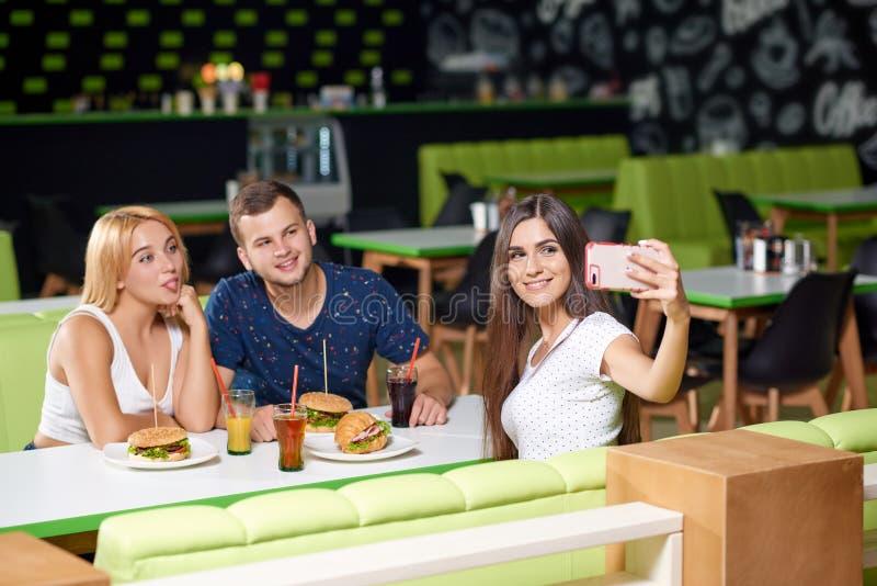 Selfie de mantimento moreno do telefone e da tomada com amigos foto de stock royalty free